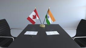 Drapeaux du Canada et de l'Inde et papiers sur la table Négociations et signature d'un accord international 3D conceptuel illustration libre de droits