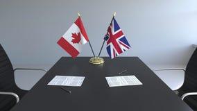 Drapeaux du Canada et de la Grande-Bretagne et papiers sur la table Négociations et signature d'un accord international illustration stock