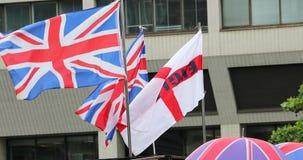 Drapeaux du Royaume-Uni au vent avec parapluies à Londres banque de vidéos