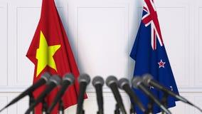 Drapeaux du Vietnam et du Nouvelle-Zélande à la conférence de presse internationale de réunion ou de négociations animation 3D banque de vidéos