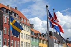 Drapeaux et maisons colorées à Copenhague, Danemark Photographie stock libre de droits