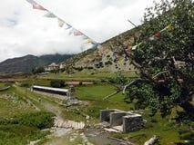 Drapeaux et roues de prière près d'une petite ville de l'Himalaya Photos libres de droits