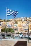 Drapeaux grecs, bateaux et maisons néoclassiques colorées dans la ville de port de l'île de Symi Symi, Grèce image libre de droits