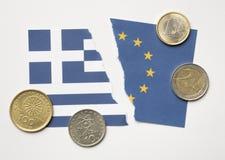 Drapeaux grecs et européens déchirés avec des pièces de monnaie d'euros et de drachme Images libres de droits
