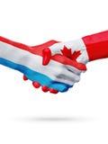 Drapeaux Luxembourg, pays de Canada, concept de poignée de main d'amitié d'association Photographie stock libre de droits