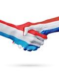 Drapeaux Luxembourg, pays néerlandais, concept de poignée de main d'amitié d'association Photographie stock