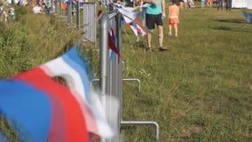 Drapeaux multicolores sur la barrière déplaçant lentement le grillage de vent sur l'aire de pique-nique banque de vidéos