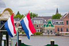 Drapeaux néerlandais ondulant à Zaandam, terre des moulins à vent Photographie stock