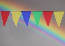 Drapeaux triangulaires colorés multi accrochant dans le ciel à un extérieur contre le contexte d'un arc-en-ciel Image stock