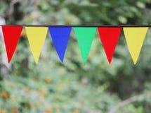 Drapeaux triangulaires colorés multi accrochant dans le ciel à un extérieur contre le contexte d'une herbe verte Photo libre de droits