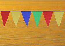 Drapeaux triangulaires colorés multi accrochant dans le ciel à un extérieur sur le fond de l'eau d'or Photo libre de droits