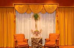 Draped curtains and chairs. A view of heavy, luxurious drapes and curtains with soft chairs in front of a large window stock images