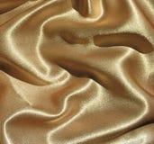 Draped gold satin background. Beautiful golden satin fabric with drapery. Background Stock Photos