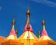 Draped golden chedis soar into blue sky. At Wat Sang Lan a buddhist temple in Pathum Thani province of Thailand Royalty Free Stock Photography