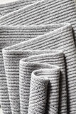 Draped melange gray woolen knitted fabric as background. Stock Photos