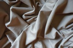 Draped beige viscose and polyester fabric. Draped simple beige viscose and polyester fabric Stock Images