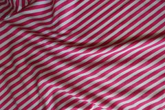 Draped striped fabric in pink and white. From above Stock Photo