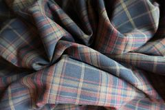Draped thick plaid fabric in subdued colors. Draped thick plaid fabric  in subdued colors Royalty Free Stock Images