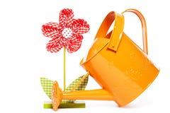 Drapeje a flor e uma lata molhando alaranjada imagem de stock