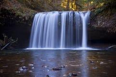 Draperende waterval met lichtblauwe bezinning in water. Stock Foto's