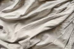 Drapery. Draped beige linen closeup as a background Stock Photo