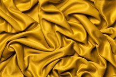 Drapery fabric gold. Wavy background. Royalty Free Stock Image