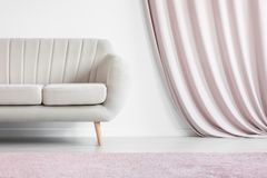 Drapes in cozy living room. Beige settee against white wall with pink drapes in cozy living room interior with pastel carpet Royalty Free Stock Image