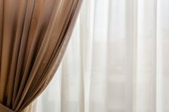 Drapes. Luxury beige drapes in a big luminous hall Royalty Free Stock Photography