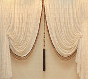 Drapes. Vintage drapes with gold embellishments hanging from a wall Stock Images