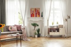 Drapes at windows and poster in white living room interior with couch and cupboard. Real photo. Concept royalty free stock photos