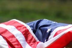 Drapierte amerikanische Flagge mit grasartigem Hintergrund Lizenzfreie Stockfotografie