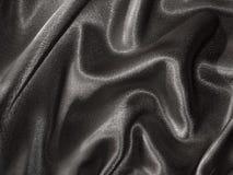 Drapierter schwarzer Satinhintergrund Stockfoto