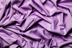 Draping fabric cloth shiny purple lilac. Wavy background. Stock Image