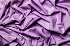 Draping fabric cloth shiny purple lilac. Wavy background. Stock Image