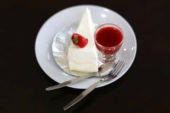 Drappeggi con crespo il dolce con la salsa della fragola sulla tavola nera Immagini Stock