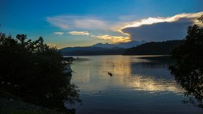 Drastische Ansicht des Sonnenuntergangs mit Gebirgsseehintergrund stockbild