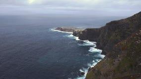 Drastische Ansicht von den Wellen, die auf den Klippen entlang der Küste, Neigung zusammenstoßen stock video footage