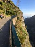 Drastische Berglandschaft mit zwei Leuten, welche die Ansicht bewundern lizenzfreie stockbilder
