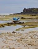 Drastische Beschaffenheit des Strandes während der Ebbe, die gelegentlichem Adermuster mit hölzernen Booten und Haus im Hintergru Lizenzfreie Stockfotos