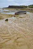 Drastische Beschaffenheit des Strandes während der Ebbe, die gelegentlichem Adermuster mit hölzernen Booten und Haus im Hintergru Lizenzfreies Stockfoto