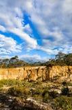 Drastische gelbe Sandsteinklippe gegen bewölkten Himmel Stockfotografie