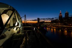 Drastische im Stadtzentrum gelegene Skyline bei Sonnenuntergang - verlassene Cuyahoga-Fluss-Hubbrücke in Cleveland, Ohio Stockfotografie