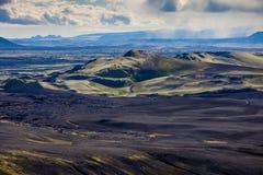 Drastische Island-Landschaft von Kratern vulkanischen Spalts Laki mit einem grünen Hügel und der schwarzen Lavaaussehung wie ein  lizenzfreie stockfotos