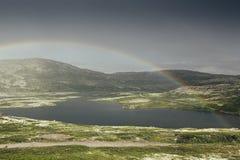 Drastische Landschaft mit schönem Regenbogen über arktischen Wiesen, Berg und See Stockfoto