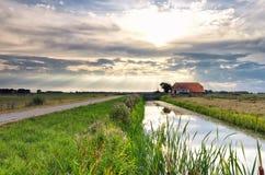 Drastische Sonnenstrahlen über Bauernhaus und Fluss lizenzfreies stockbild