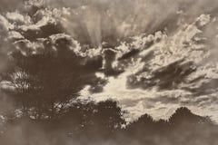 Drastische Sonnenuntergangsonnenaufgangstrahlen des Lichtes bewölkt Retro- Weinlese des Sepia Lizenzfreies Stockbild