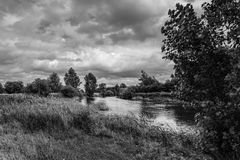 Drastische Szene von einem weithin bekannten Fluss und von Wiese gesehen vor einem Sturm lizenzfreies stockfoto