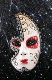 Drastische und mysteriöse Halbmondkarnevalsmaske und schwarzer Funkelnhintergrund Stockbilder