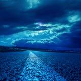 drastische Wolken über Asphaltstraße im dunklen Mondschein lizenzfreies stockbild