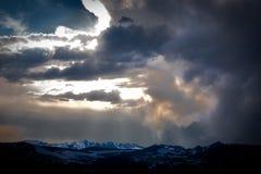Drastische Wolken über Schnee mit einer Kappe bedeckten Bergen Stockbild